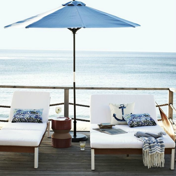 Coastal outdoor space with sun loungers and umbrella