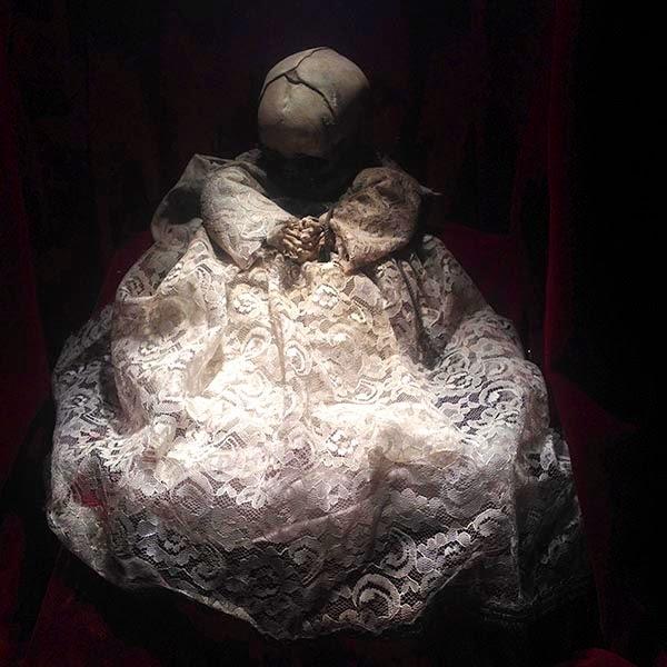 Momia de un niño pequeño vestido de santo en el Museo de las Momias de Guanajuato. Nuestro planeta, lamentablemente, cada vez se  parece más a los cuerpos secos, rígidos y duros  de las momias que tengo delante. Un planeta  cada vez mas seco, mas duro y más rígido. La dureza del metal y del concreto está  sustituyendo a la suavidad de la tierra. El polvo  seco de los desiertos sustituye a la humedad de  los bosques. La rígidez de las máquinas está  sustituyendo a la flexibilidad de los seres vivos.