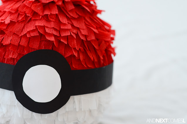 Close up of white crepe paper and red crepe paper streamers on a DIY pokeball pinata