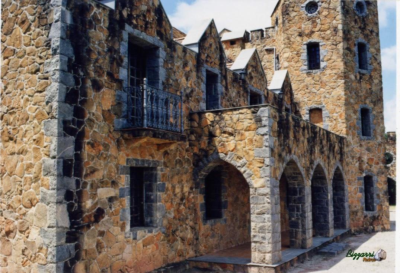 Detalhe da parede de pedra rústica na construção desse castelo de pedra com os pilares de pedra, a torre de pedra com o pórtico de pedra.