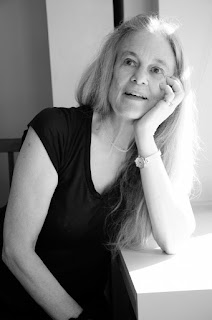 Image of Sharon Olds in black and white. Sharon is sitting by a window with one arm resting on the windowsill. She rests her head on her hand and looks off into the distance, her mouth open as if she is in the middle of a conversation.