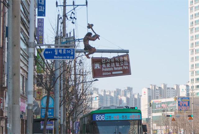 Cavernícola de cartón piedra sobre una señal de tráfico en Corea