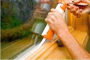 Caulking a window.