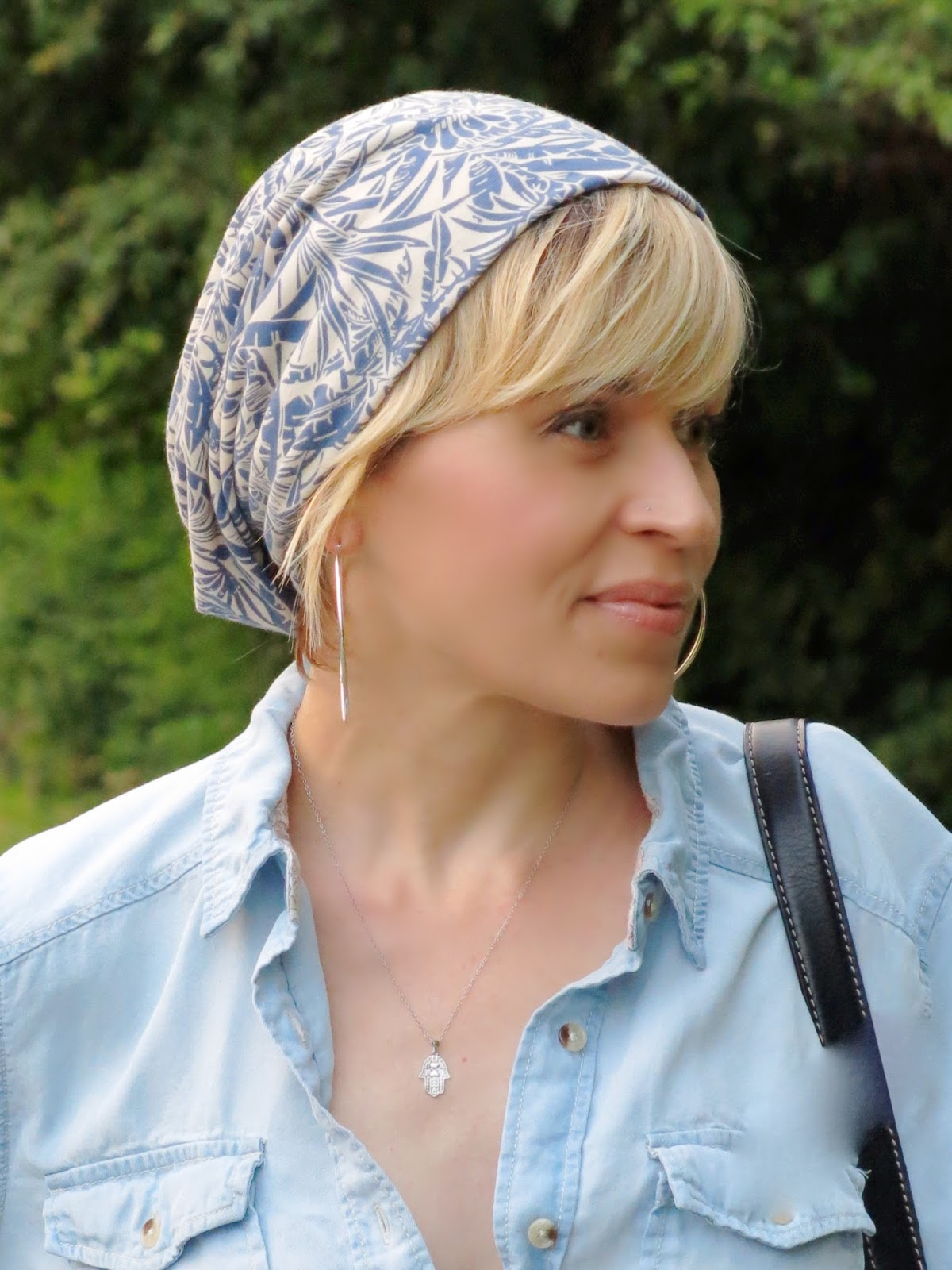 chambray shirt, patterned beanie, and hoop earrings