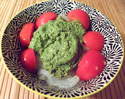 Pesto on shiritaki noodles garnished with tomato wedges