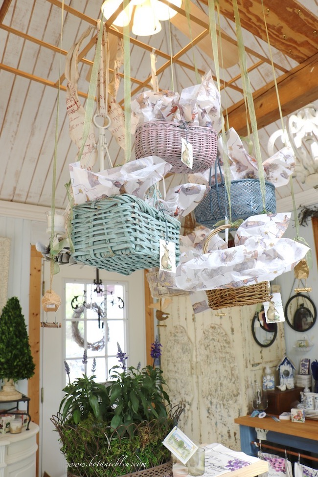 Spring baskets in pastel colors as ceiling display above a table in the garden shed