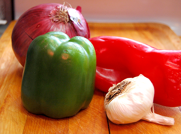 purple onion, green bell pepper, red bell pepper, whole garlic on a cutting board