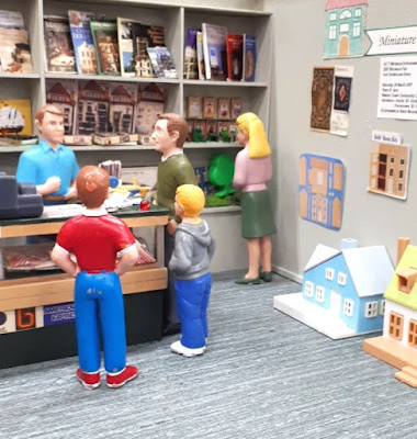 Detail of a one-twelfth scale miniature dolls' house shop with four males having a conversation around the counter, and a woman looking at a display of boxed kits at the back of the shop.