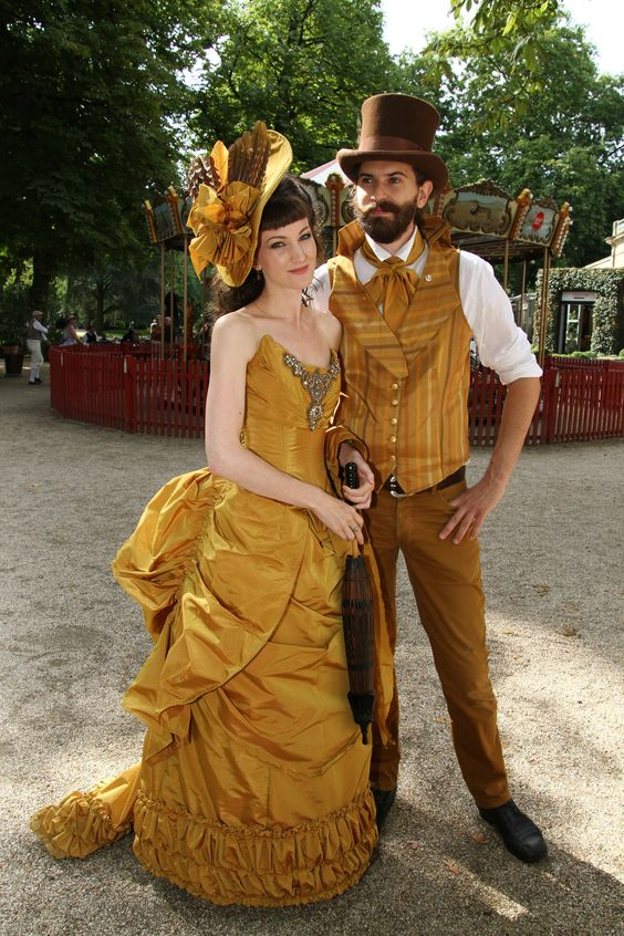 Man and woman wearing matching victorian costumes in gold/yellow color. coordinating steampunk and victorian costumes for couples