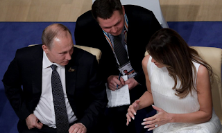 Melania Trump sits beside Putin after Trump confronts him about election interference, which Putin denies