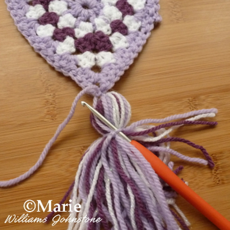 using a crochet hook to tidy up strands for a neater crocheted project