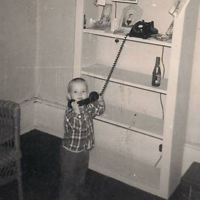 Jimmy at 18 months old standing next to shelves holding telephone to ear