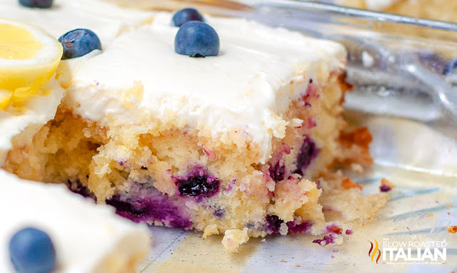 plated slice of frosted lemon cake with blueberries