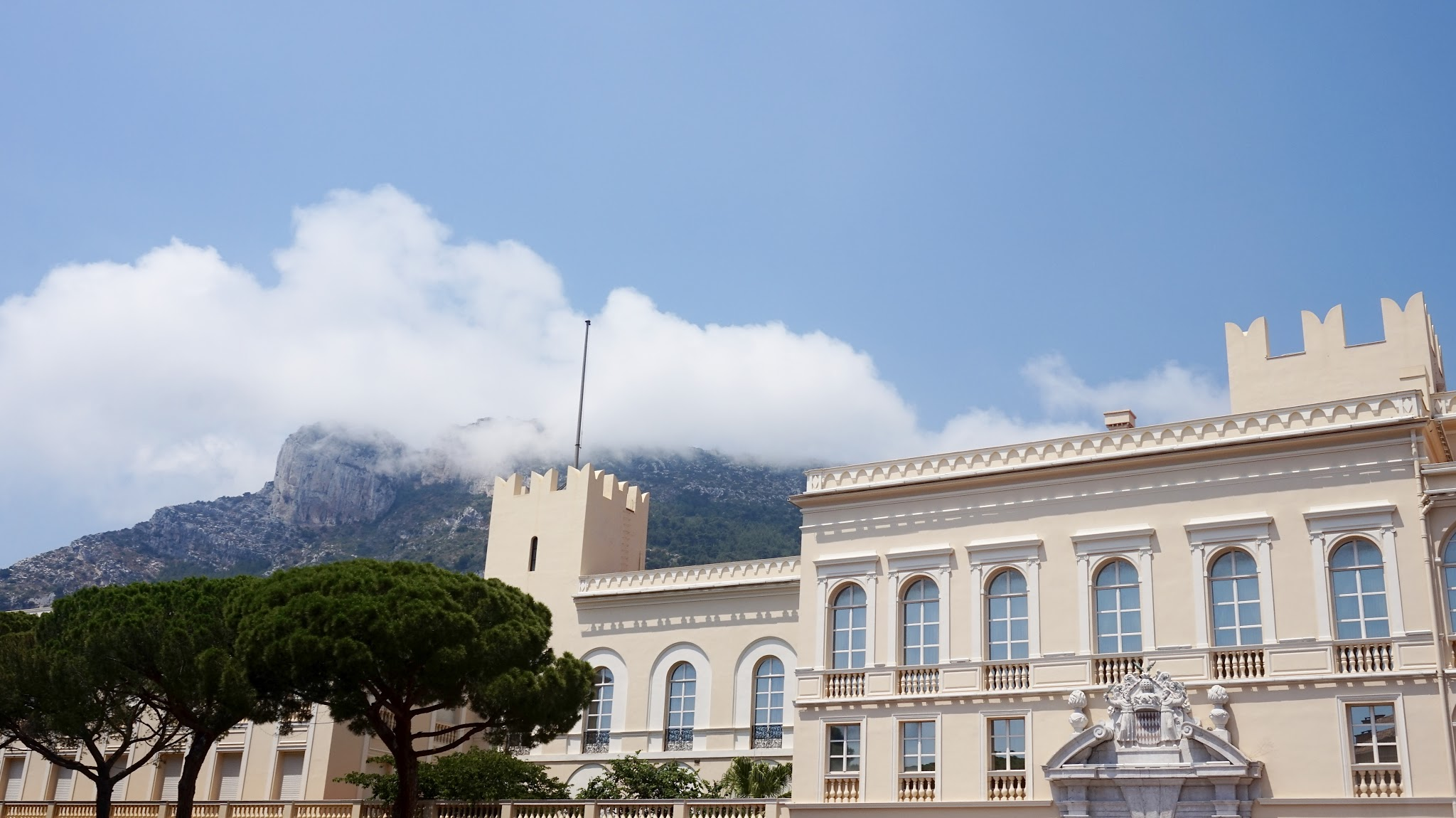 a yellow coloured palace building, with mountains in the background, a blue cloudy sky