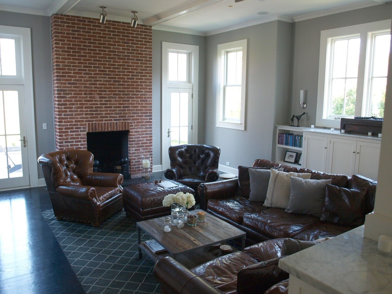 Industrial farmhouse family room with red brick fireplace and leather furniture - Hello Lovely Studio
