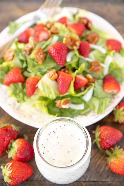 poppy seed dressing in a jar with strawberry salad in the background