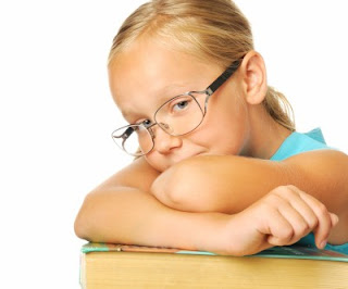 Sad girl wearing glasses with arms crossed on stack of books