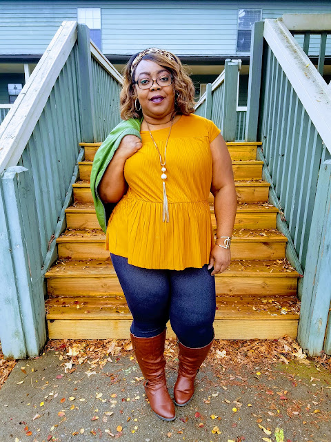 Curvy blogger with mustard blouse, green bomber jacket, denim jeggings, cognac boots.