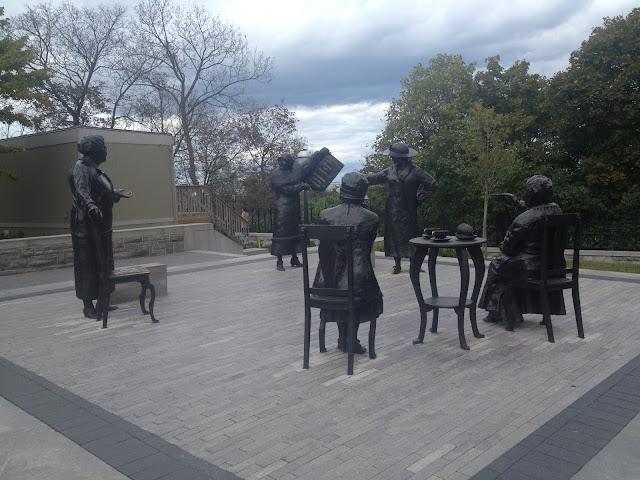 """Essas estatuas representam as mulheres ativistas que lutaram para que a mulher também tenha seu espaço no senado. A que está de pé segura um livro que diz """"mulheres são pessoas"""" com a data de 18 de outubro de 1929."""