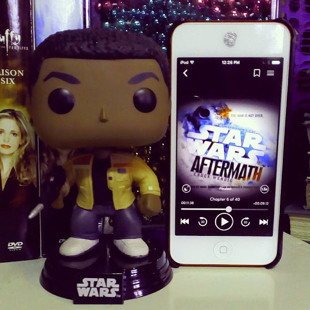 A large-headed Funko Pop bobblehead of Finn from Star Wars stands beside a white iPod with Aftermath's white cover on its screen. The cover features the title and author's name at an angle across an image of the Death Star exploding.