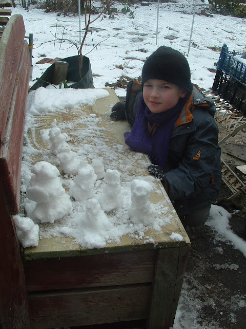 A little boy posing with a posse of tiny snowmen on a garden bench