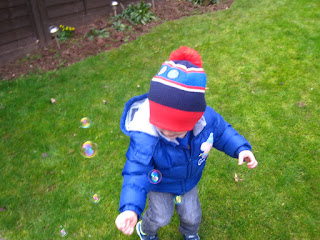 Little boy playing with bubbles in the garden