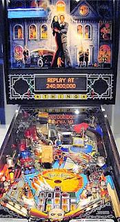 Detalle del pinball de la familia Addams de 1992. La imagen muestra el marcador con Morticia y Gomez Addams y la mesa de juego con pasillos, rampas, dianas y cuatro flippers.