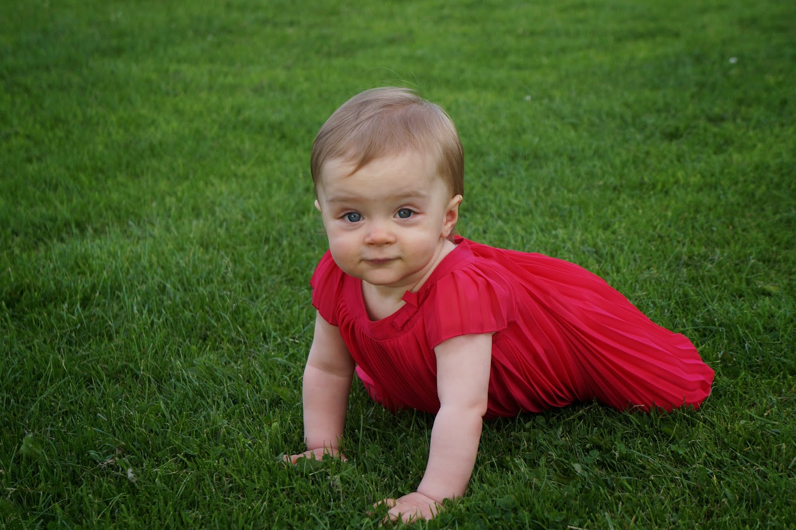 baby in red dress on grass