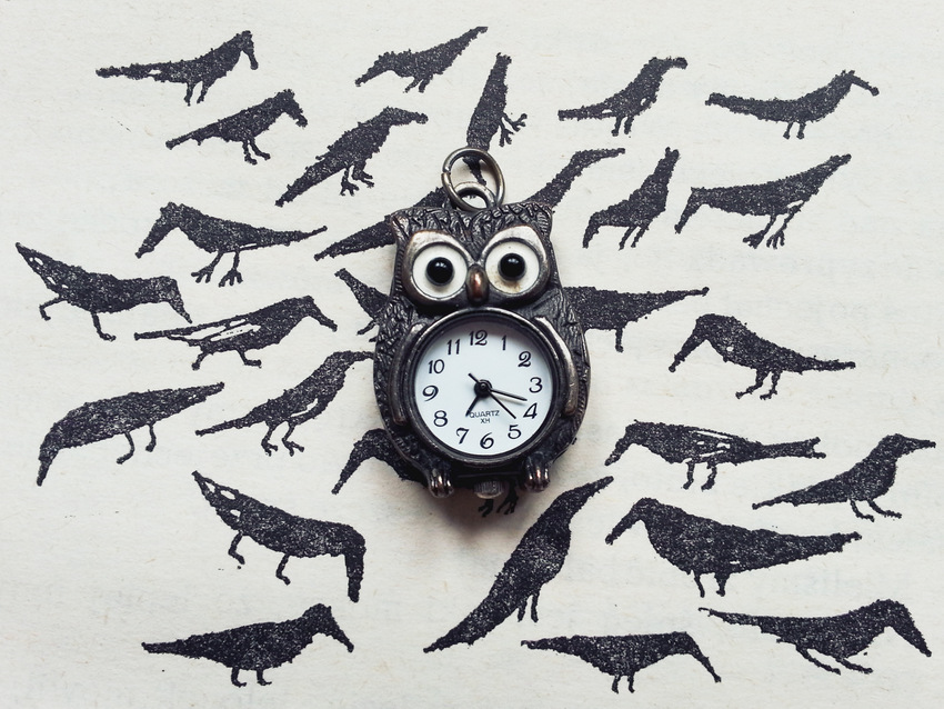 """Wisiorek-zegarek z sową na tle książki """"Najwyższa góra"""" Mieczysławy Buczkówny z 1988 roku, ilustracje:Andrzej Strumiłło"""