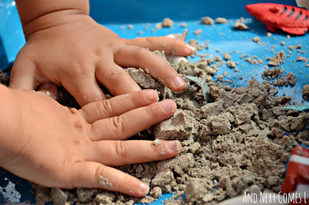 Toddler playing with sand foam sensory dough