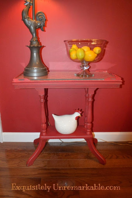 A red painted table with rooster lamp, lemons in a bowl and small red ceramic chicken on bottom shelf