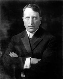 Black and white photo of a grim-faced William Randolph Hearst with his arms crossed in front of him