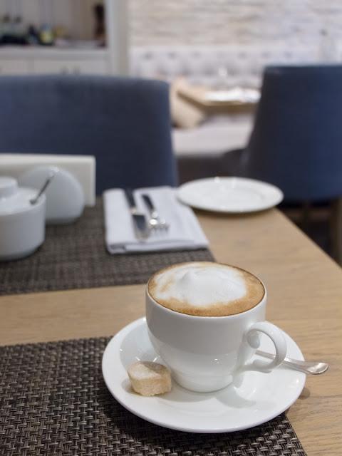 Чашка капучино с печенькой в интерьере французского кафе