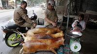 Men grilling dog in Vietnam