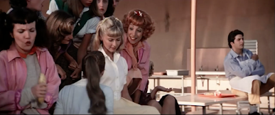 Who is this lonely background extra from the movie, Grease? Why is he stalking Olivia Newton-John. Is he a ghost?