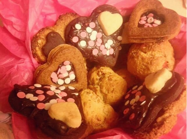 Valentines day biscuits or cookies with chocolate frosting in heart shapes. Chocolate shortbread, scones and chocolate chip.