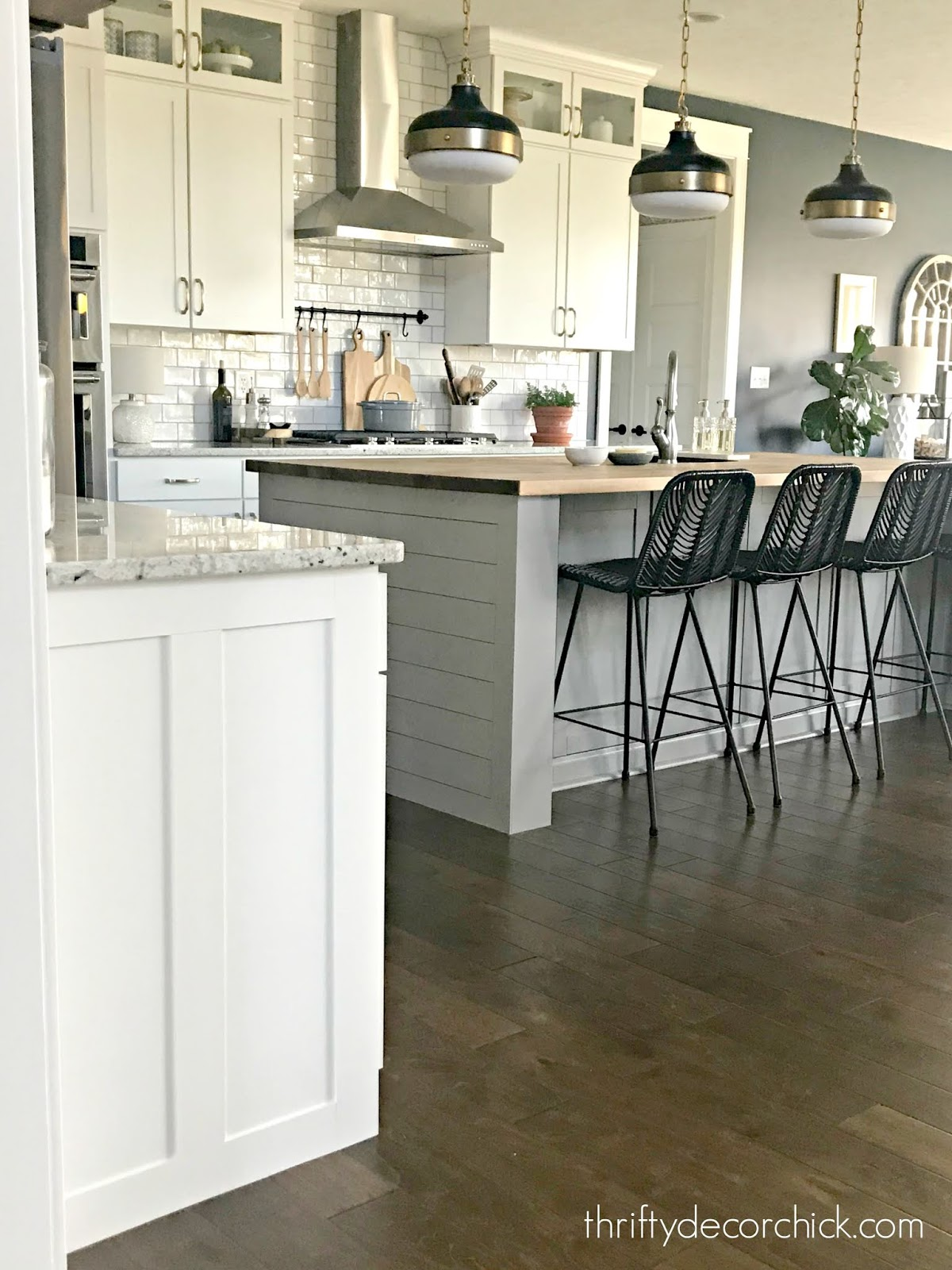 Light gray island, black stools, white kitchen