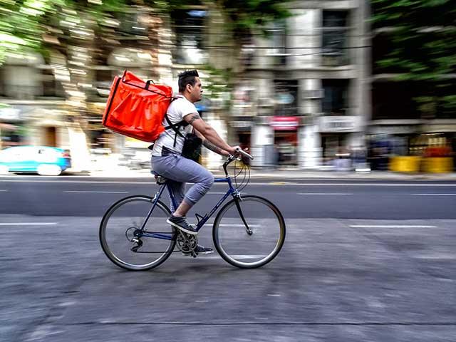 Joven delivery en bicicleta por la ciudad