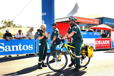 Three paramedics in their green uniforms congregate at the McLaren Vale starting line in the crisp morning summer sun. Two are standing with one sitting on a yellow pushbike. Race spectators are gathering behind the blue, white and red barriers behind the paramedics.