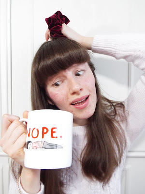 """Ellie depicting the absolute image of stress, scarcely holding up a cup of tea in a Gemma Correll mug, with the word """"nope"""" written across it, with imagine of a lady lying on floor; attempting to tie hair up in bobble; and sporting a stressed expression"""