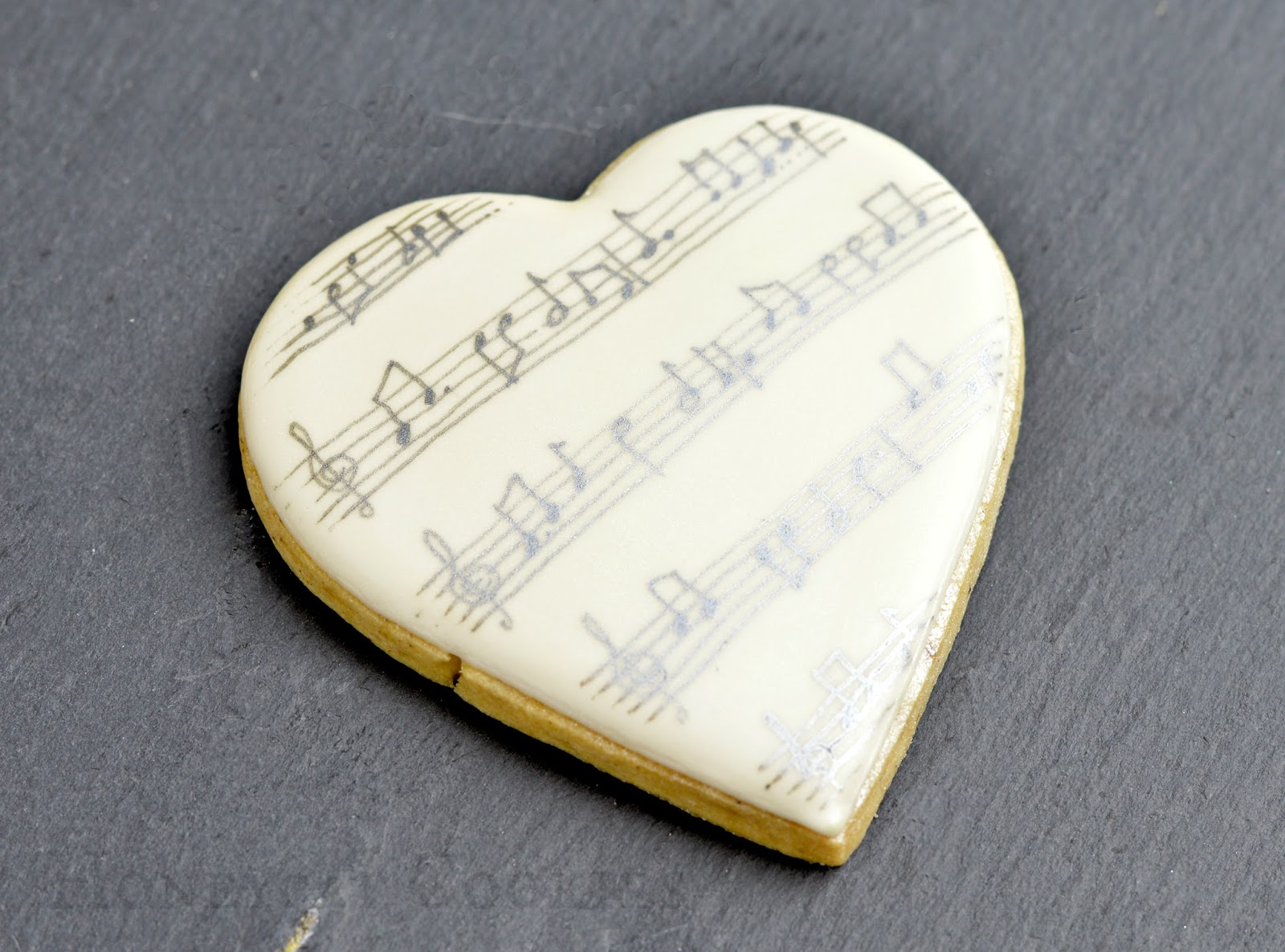Hand drawn musical notation in food colour on heart shaped cookie for Valentine's Day.