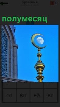 На фоне голубого неба стоит шпиль с полумесяцем на верху, внутри которого находится луна