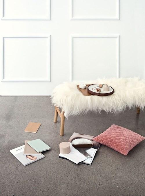 Helle Holzbank dekotiert mit einem warmen, weichen Schafsfell