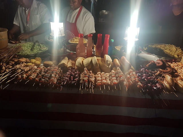 A variety of seafood skewers and some traditional foods including cassava at a streetfood vendor at Forodhani Gardens