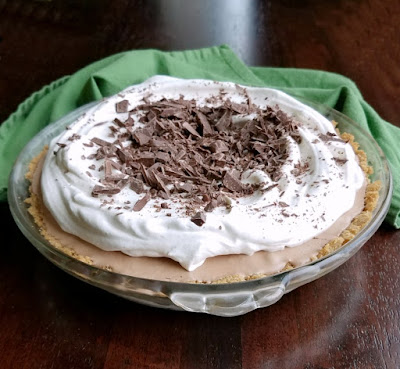 whole frozen mint meltaway pie (aka frango mint pie) topped with whipped cream and chopped frango mints