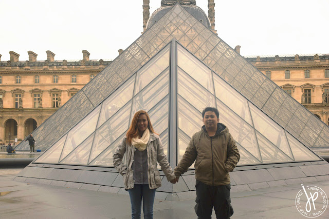 couple holding hands, glass pyramid background