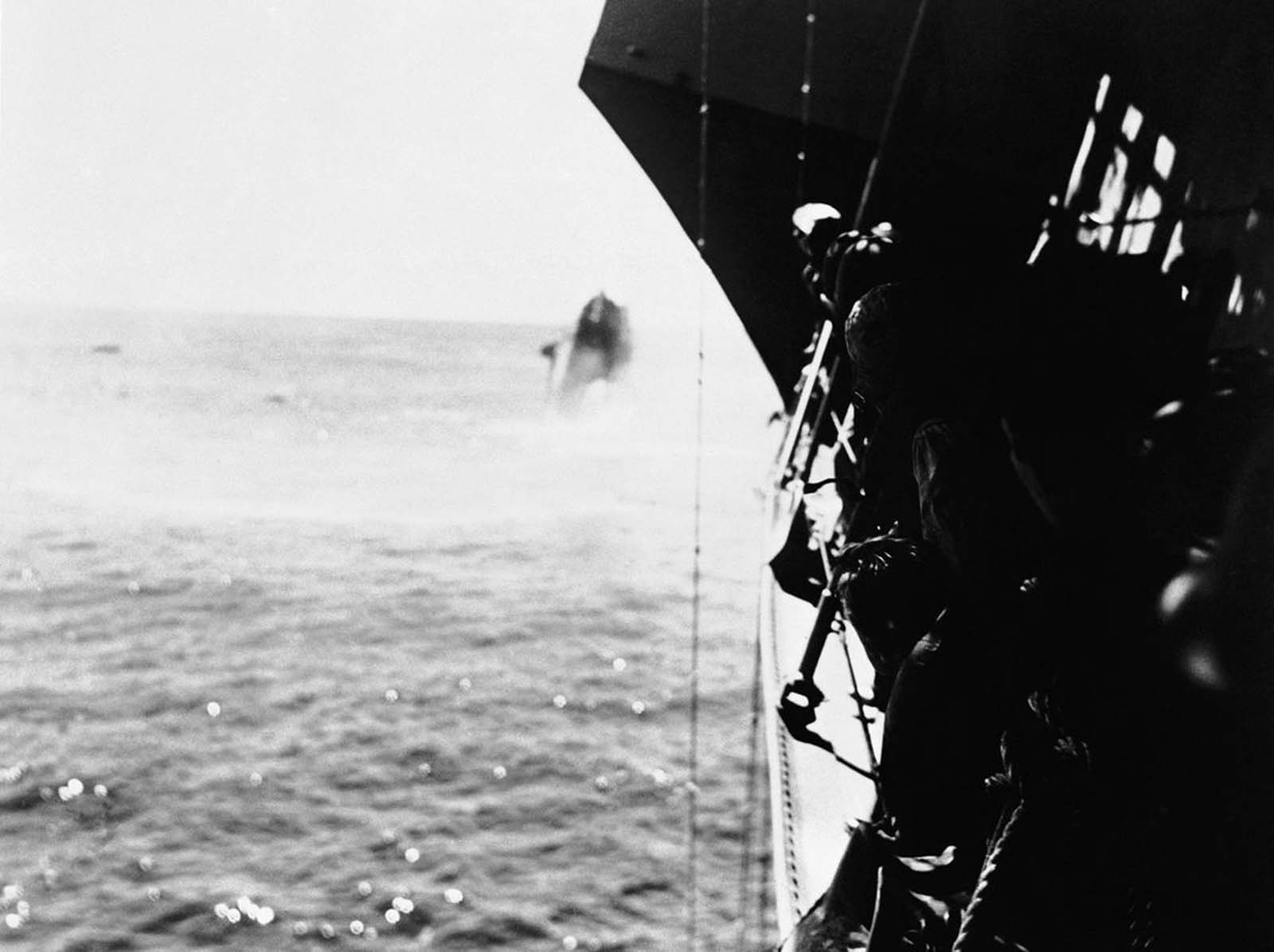 The United States destroyer Hammann, background, on its way to the bottom of the Pacific after having been hit by a Japanese torpedo during the battle of Midway, in June of 1942. The Hammann had been providing auxiliary power to damaged USS Yorktown while salvage operations were underway. The same attack also struck the Yorktown, which sank the following morning. Crewmen of another U.S. warship, foreground, line the rail as their vessel stands by to rescue survivors.