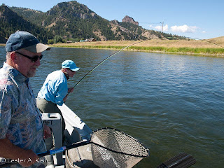 Angler hooked up with a Missouri River rainbow while guide Mike Geary waits with the net