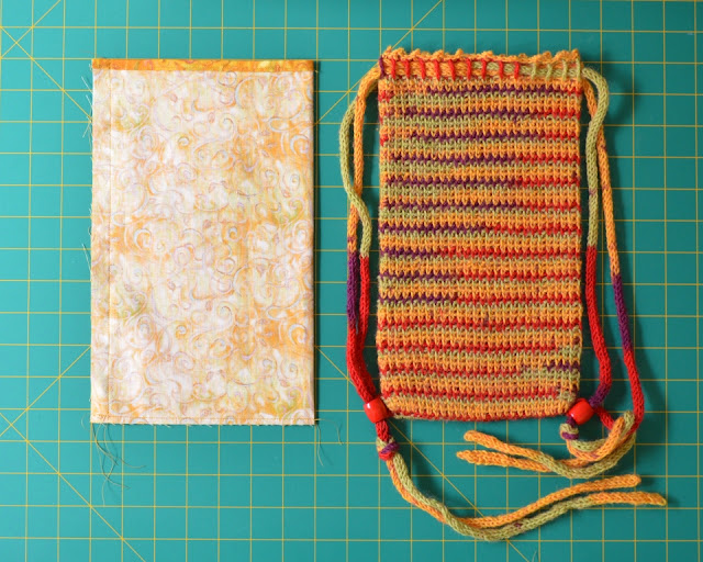 The lining is laid out next to the crocheted bag on the grid.