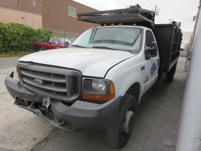 Damaged stake bed work truck before repairs at Almost Everything Auto Body